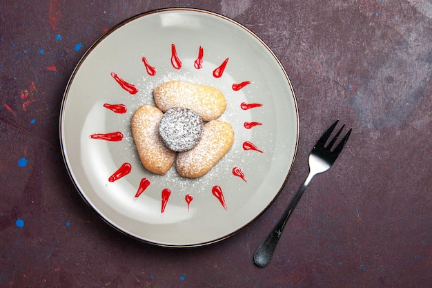 Bovenaanzicht van lekkere koekjes met suikerpoeder en rood glazuur in de plaat op zwart
