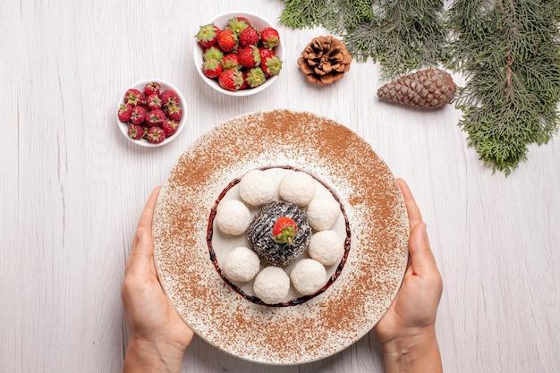 Bovenaanzicht van lekkere kokossnoepjes met cacaocake op witte tafel