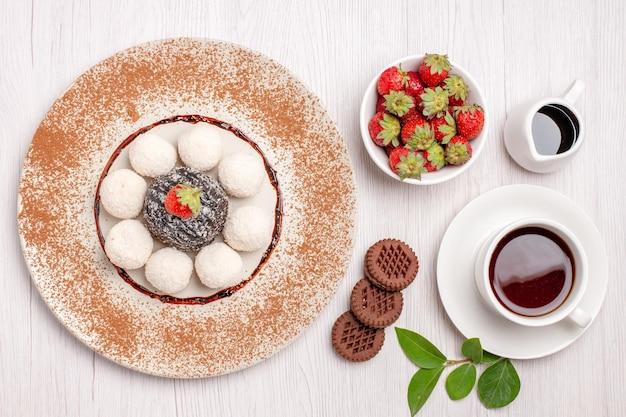 Bovenaanzicht van lekkere kokossnoepjes met chocoladetaart en kopje thee op wit