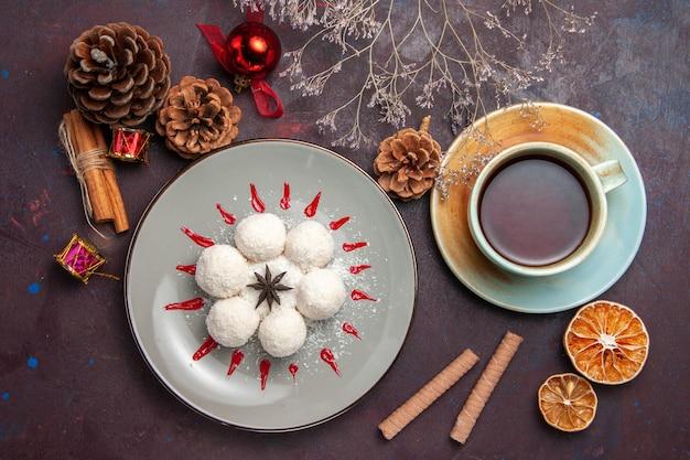 Bovenaanzicht van lekkere kokossnoepjes met kopje thee op zwart