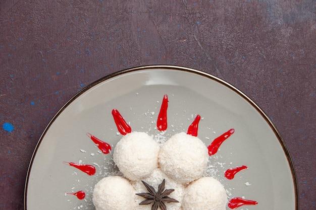Bovenaanzicht van lekkere kokossnoepjes met rode glazuur op zwart