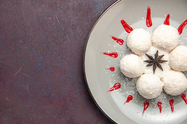 Bovenaanzicht van lekkere kokossnoepjes met rode glazuur op zwarte tafel