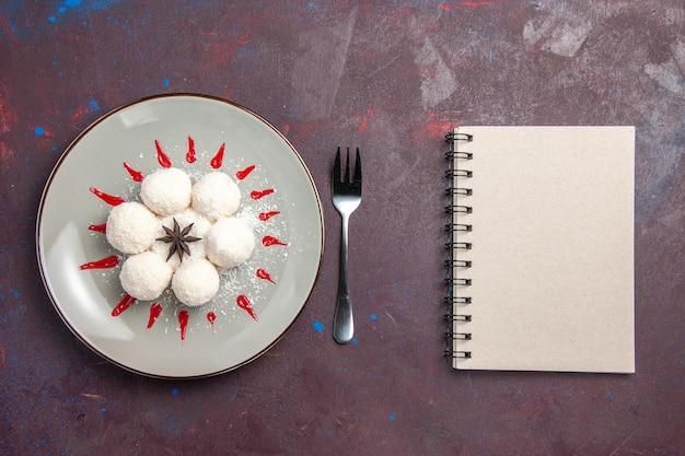 Bovenaanzicht van lekkere kokossnoepjes rond gevormd met rode glazuur op zwart