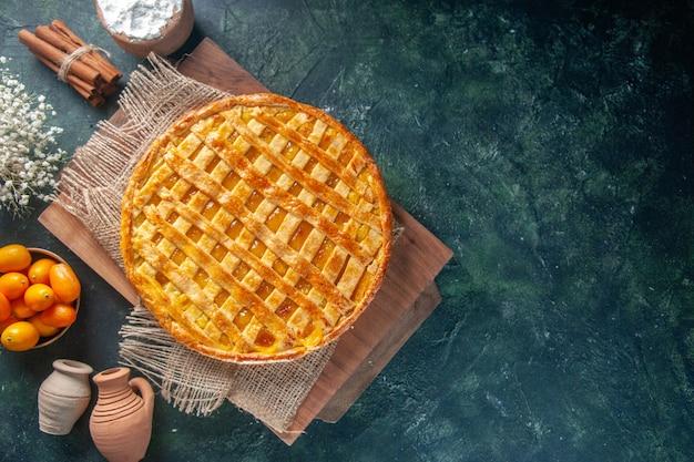 Bovenaanzicht van lekkere kumquat-taart op donkerblauw oppervlak