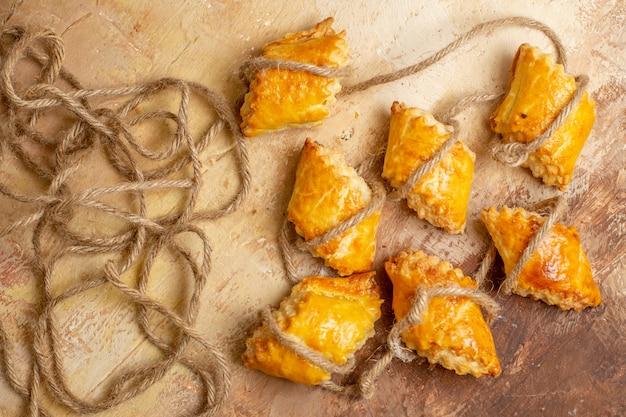 Bovenaanzicht van lekkere noten gebak met touwen op bruine achtergrond