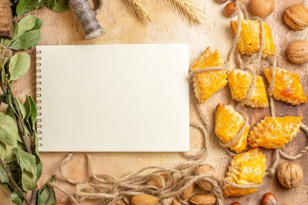 Bovenaanzicht van lekkere noten gebakjes met touwen en noten op bruine achtergrond