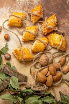 Bovenaanzicht van lekkere noten gebakjes met touwen op bruin bureau