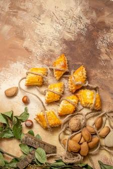 Bovenaanzicht van lekkere noten gebakjes met touwen op bruine vloer
