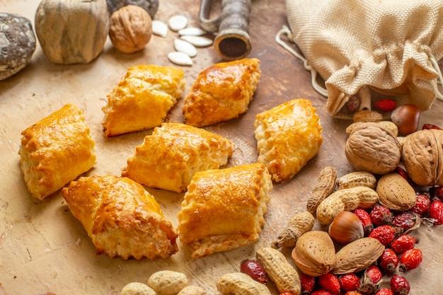 Bovenaanzicht van lekkere noten gebakjes met verse noten op bruine vloer
