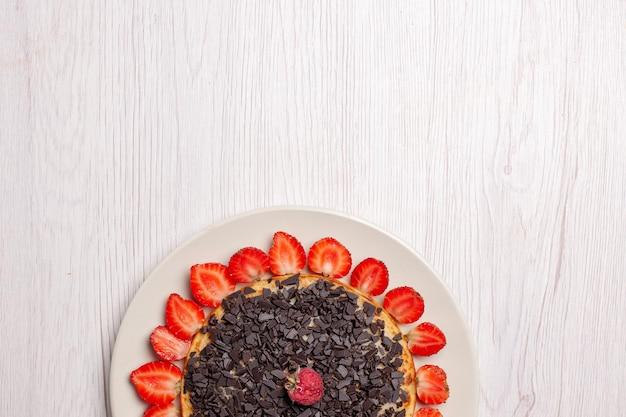 Bovenaanzicht van lekkere pannenkoeken met aardbeien en chocoladeschilfers op witte tafel