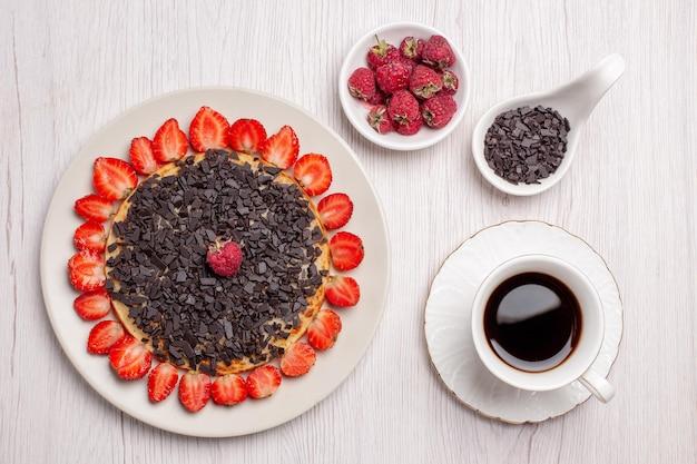 Bovenaanzicht van lekkere pannenkoeken met verse aardbeien en chocoladeschilfers op witte tafel