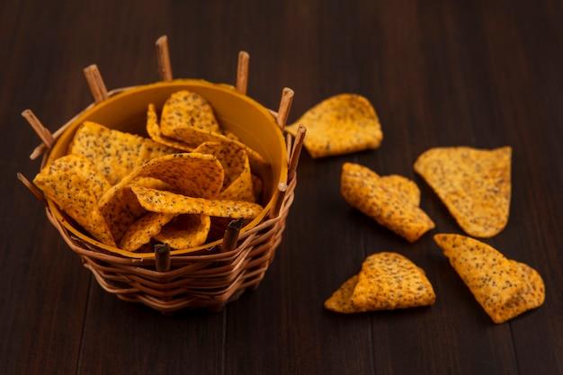 Bovenaanzicht van lekkere pittige frietjes op een emmer met frietjes geïsoleerd op een houten tafel