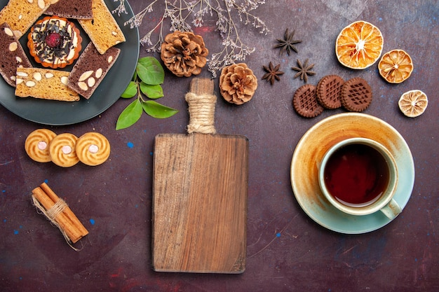 Bovenaanzicht van lekkere plakjes cake met koekjes en kopje thee op zwart