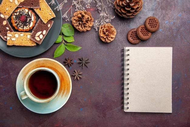 Bovenaanzicht van lekkere plakjes cake met kopje thee en koekjes op zwart