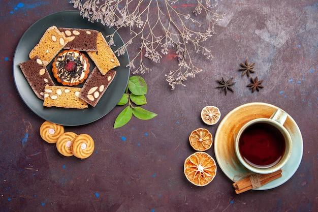 Bovenaanzicht van lekkere plakjes cake met kopje thee op zwart
