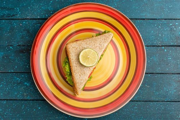 Bovenaanzicht van lekkere sandwiches met groene salade tomaten in plaat