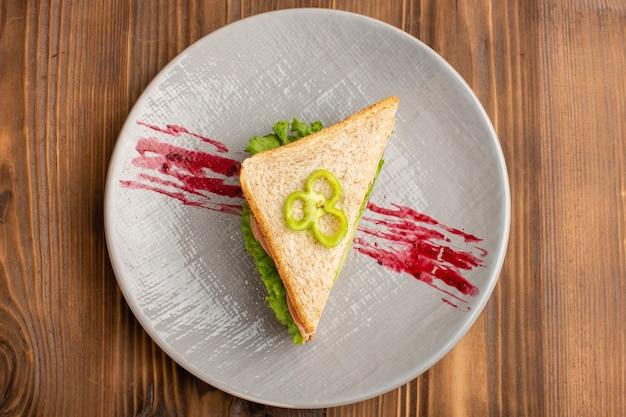 Bovenaanzicht van lekkere sandwiches met groene salade tomaten op het bruine oppervlak