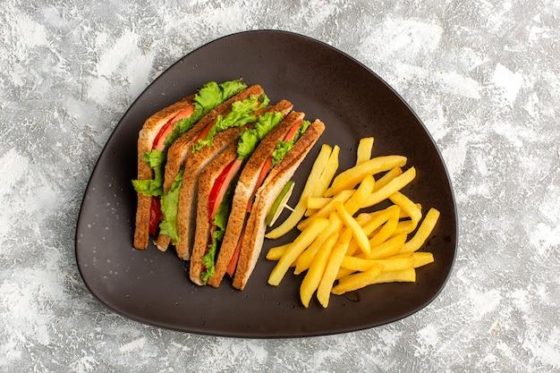Bovenaanzicht van lekkere sandwiches met groene salade tomaten samen met frietjes in donkere plaat