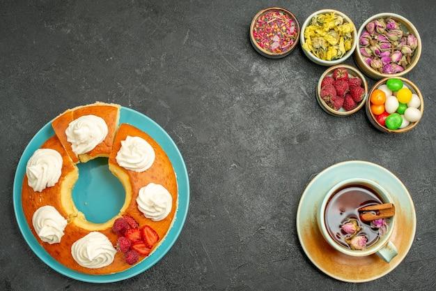 Bovenaanzicht van lekkere slagroomtaart met bloementhee en snoepjes op zwart