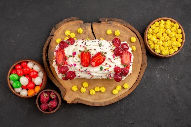 Bovenaanzicht van lekkere slagroomtaart met fruit en snoep op zwart