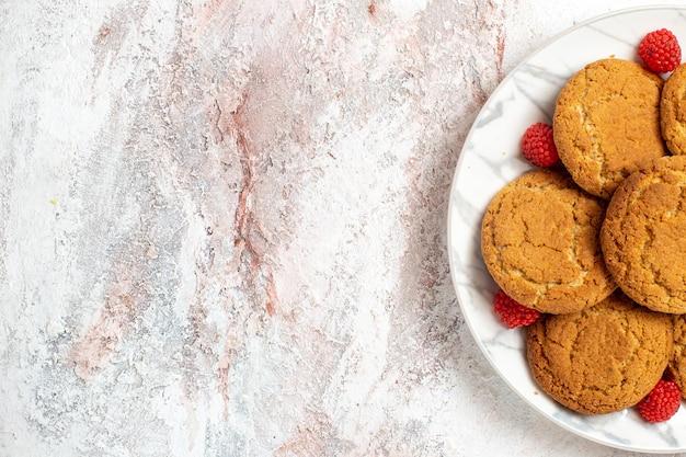 Bovenaanzicht van lekkere suikerkoekjes in plaat op wit oppervlak