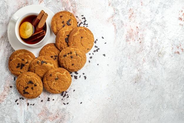Bovenaanzicht van lekkere suikerkoekjes met thee op witte ondergrond