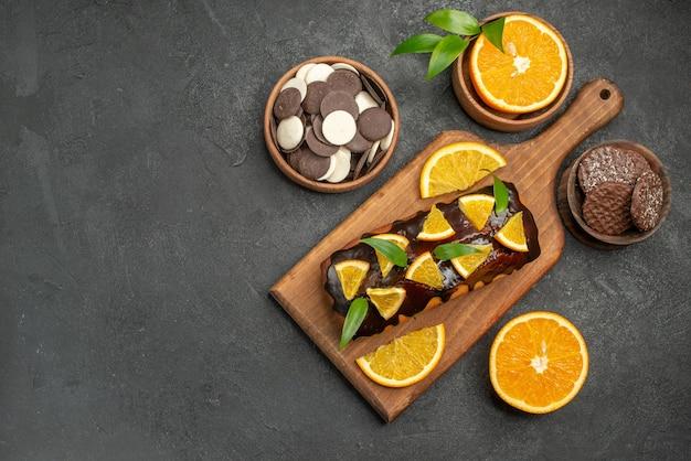 Bovenaanzicht van lekkere taarten gesneden sinaasappelen met koekjes op snijplank op zwarte tafel