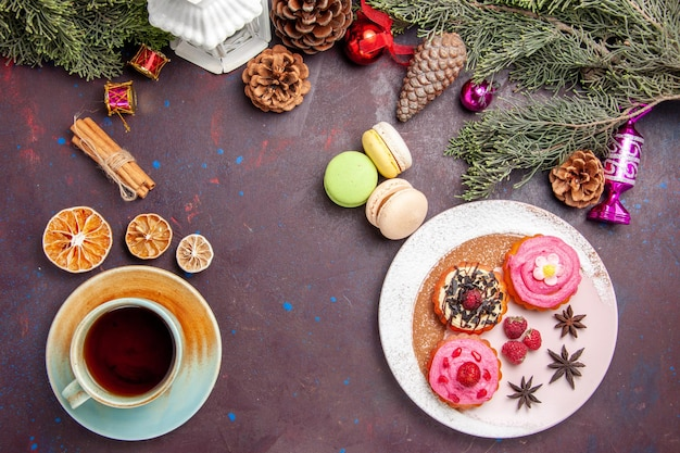 Bovenaanzicht van lekkere taarten met franse macarons en thee op zwart