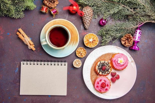 Bovenaanzicht van lekkere taarten met fruit en kopje thee op zwart