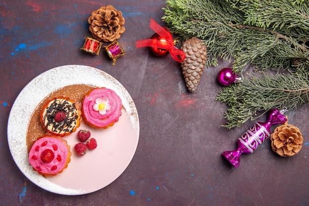Bovenaanzicht van lekkere taarten met fruit en room op zwart