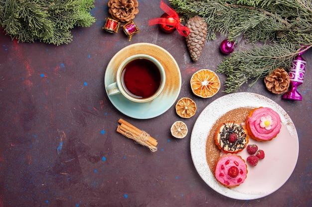 Bovenaanzicht van lekkere taarten met kopje thee op zwart