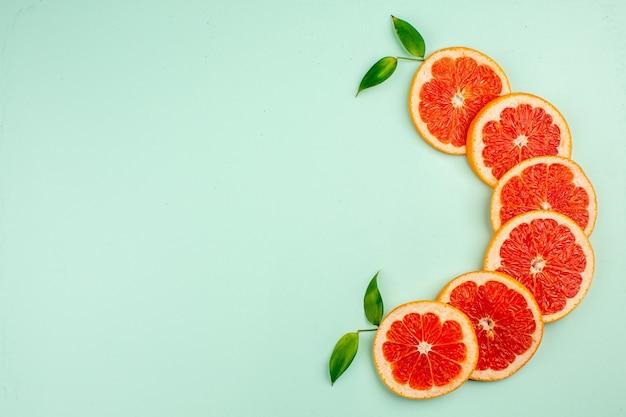 Bovenaanzicht van lekkere verse grapefruits sappige fruit plakjes op het lichtblauwe oppervlak