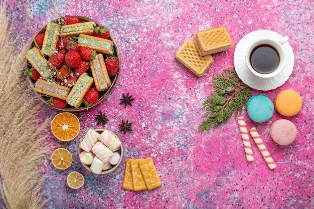 Bovenaanzicht van lekkere wafelkoekjes met franse macarons en verse rode aardbeien op roze oppervlak