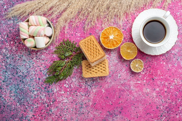 Bovenaanzicht van lekkere wafelkoekjes met kopje thee en marshmallows op roze oppervlak