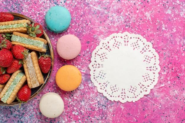 Bovenaanzicht van lekkere wafelkoekjes met macarons en verse rode aardbeien op roze oppervlak