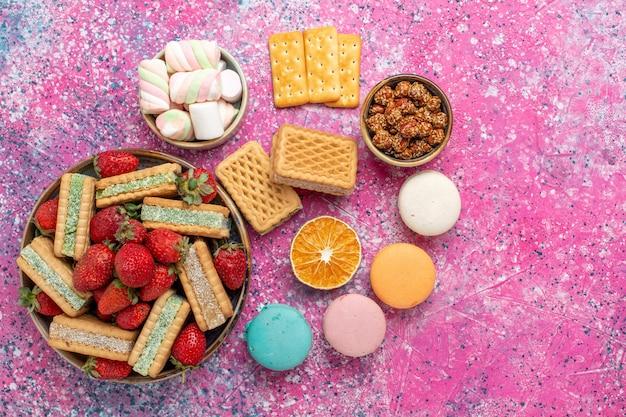 Bovenaanzicht van lekkere wafelkoekjes met marshmallows macarons en verse rode aardbeien op roze oppervlak