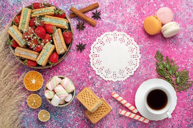 Bovenaanzicht van lekkere wafelkoekjes met verse rode aardbeien en kopje thee op roze oppervlak