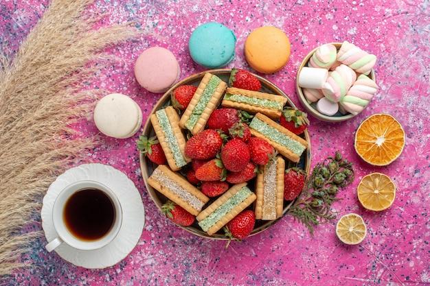 Bovenaanzicht van lekkere wafelkoekjes met verse rode aardbeien macarons en thee op roze oppervlak