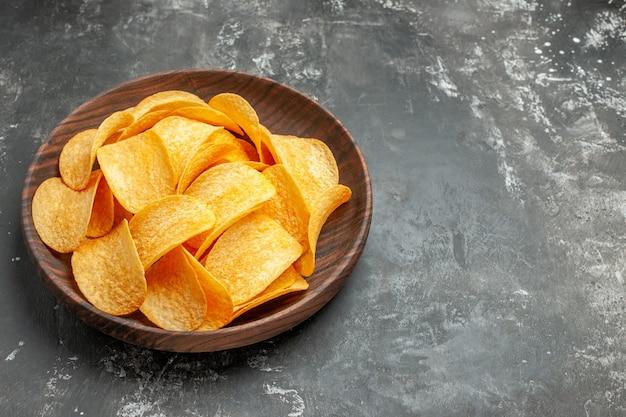 Bovenaanzicht van lekkere zelfgemaakte aardappelchips op een bruine plaat op grijze achtergrond