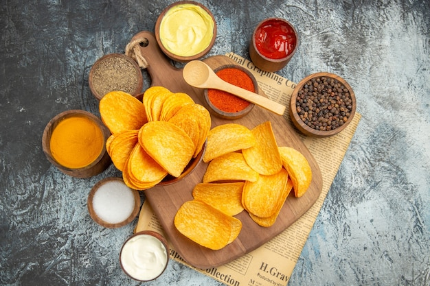 Bovenaanzicht van lekkere zelfgemaakte chips gesneden aardappelschijfjes op houten snijplank en verschillende kruiden op krant op grijze tafel