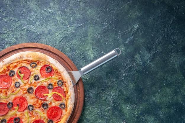 Bovenaanzicht van lekkere zelfgemaakte pizza op houten bord aan de rechterkant op donkere ondergrond