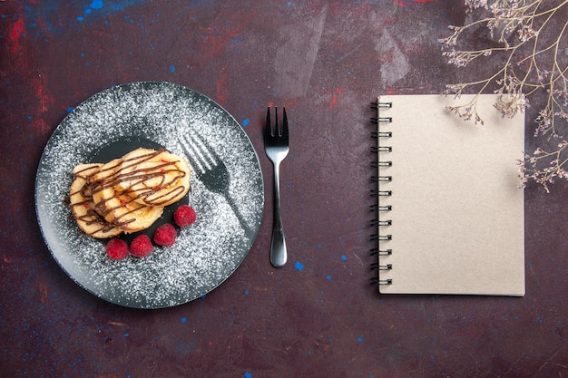 Bovenaanzicht van lekkere zoete broodjes gesneden cake voor thee in plaat op zwart