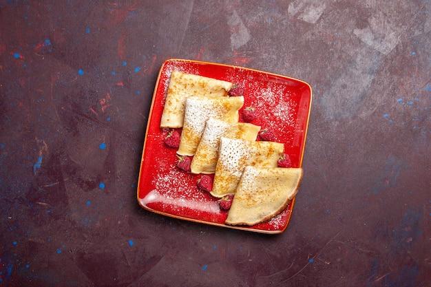 Bovenaanzicht van lekkere zoete pannenkoeken in rode plaat met frambozen op zwarte tafel