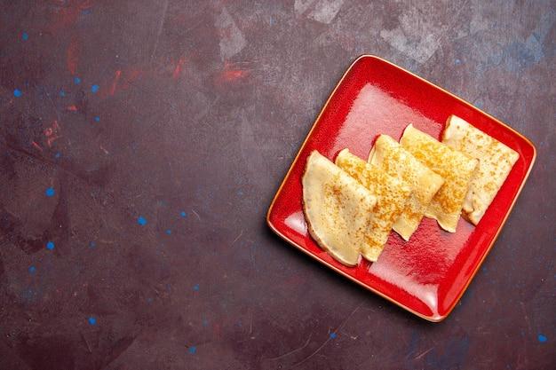 Bovenaanzicht van lekkere zoete pannenkoeken in rode plaat op donker