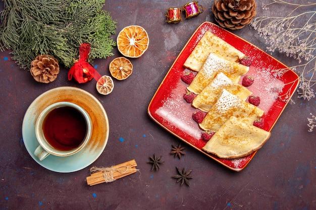 Bovenaanzicht van lekkere zoete pannenkoeken met frambozen en kopje thee op zwart