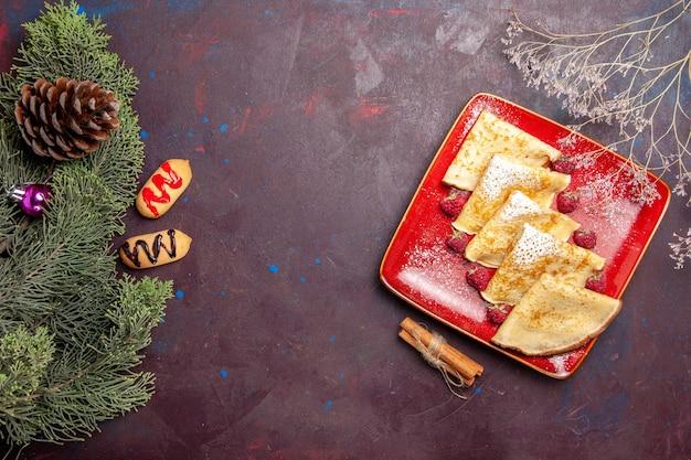 Bovenaanzicht van lekkere zoete pannenkoeken met frambozen op zwarte tafel
