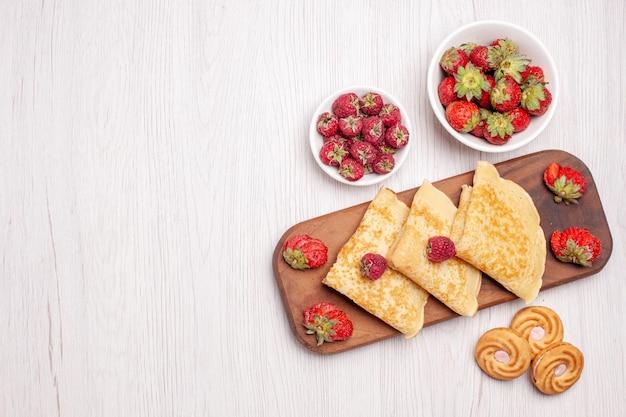 Bovenaanzicht van lekkere zoete pannenkoeken met fruit op wit