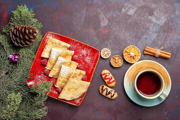 Bovenaanzicht van lekkere zoete pannenkoeken met kopje thee en frambozen op zwart