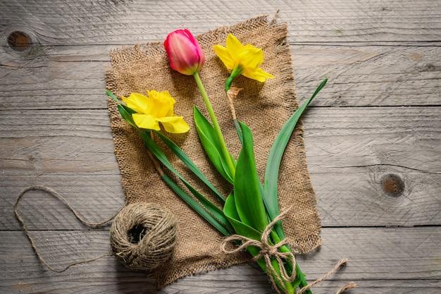 Bovenaanzicht van lente bloemen boeket. gele narcissen en roze tulp. kopieer ruimte.