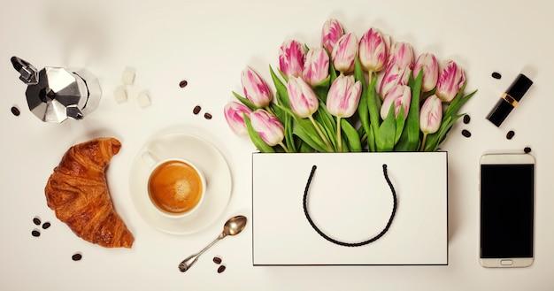 Bovenaanzicht van lentebloemen, koffie, mobiele telefoon, croissant en